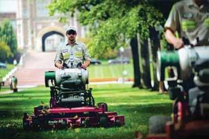 man driving a clean propane powered lawn mower