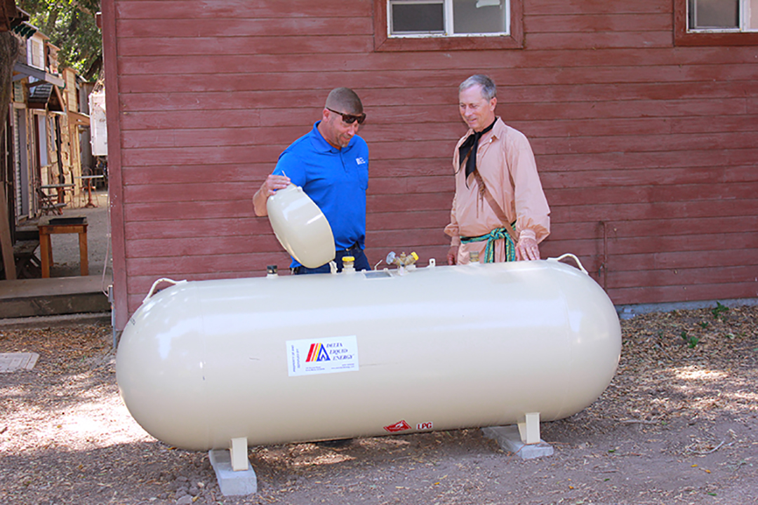 two men checking propane tank safety features