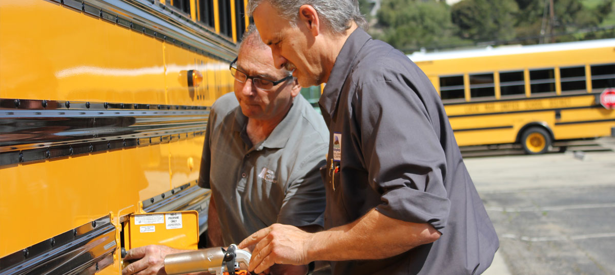 two men working on a propane powered school bus