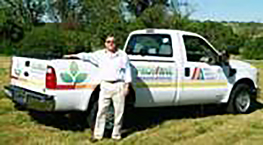 DLE President Bill Platz standing in front of propane-powered vehicle