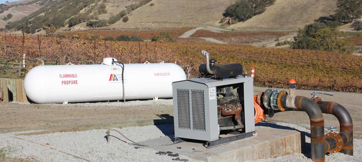 a propane tank powering a propane generator out on a grape field.