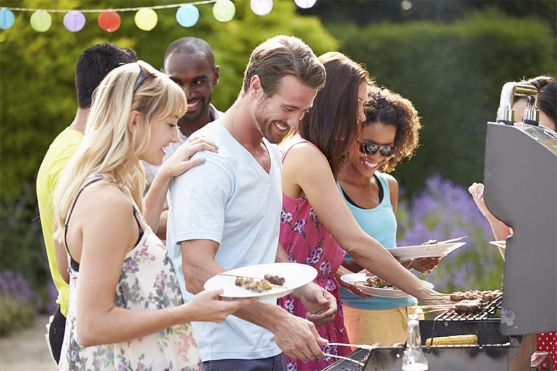 A photo of a group of people grilling food on a propane grill