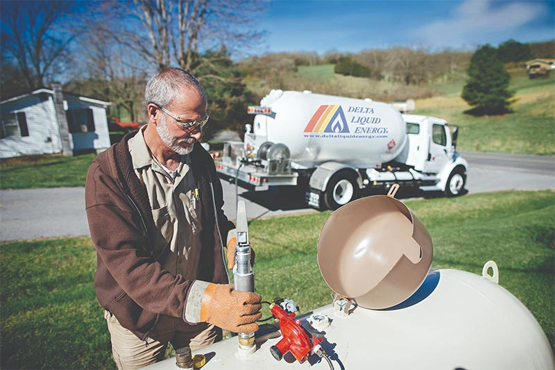 Delivery specialist showing caution while filling up residential propane tank